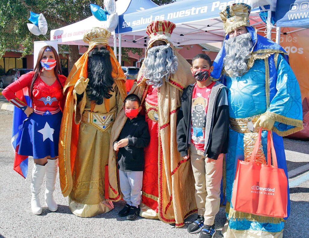 IMA Medical Group employees in three kings costume posing with kids